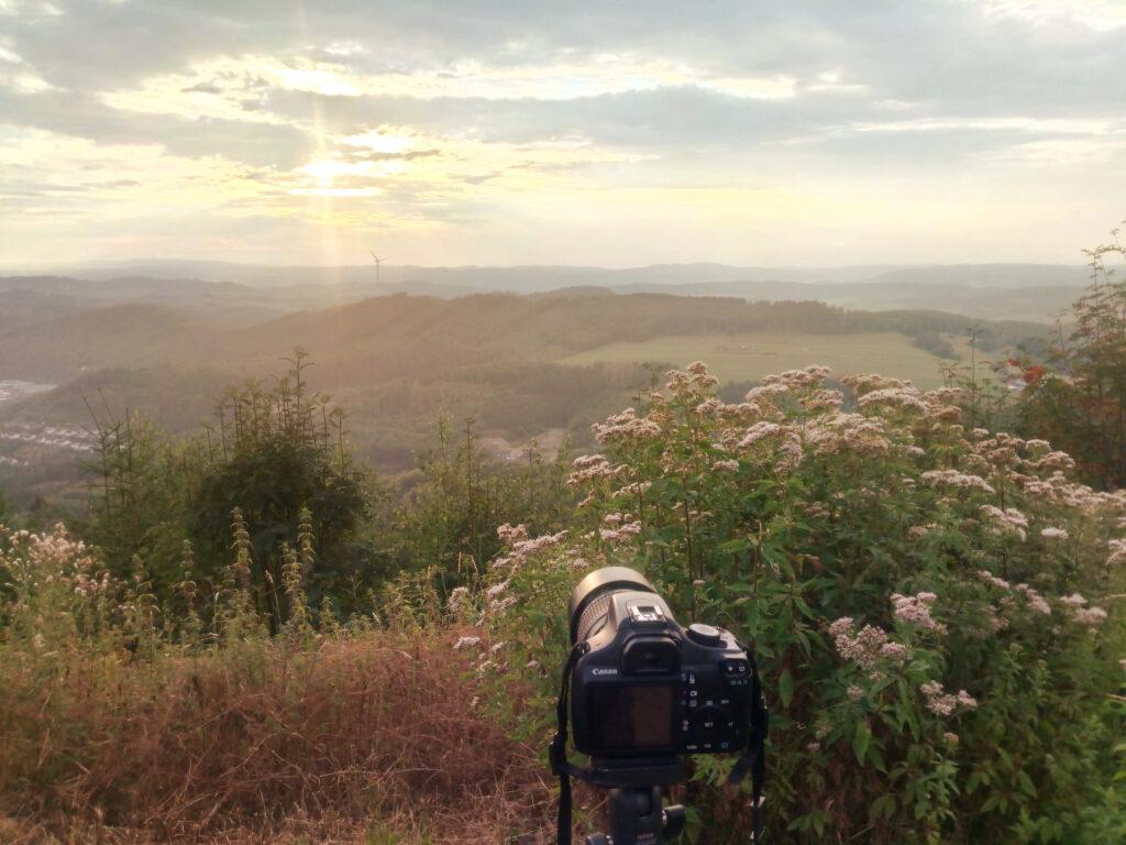 Erster Blick auf die langsam untergehende Sonne von der Kuhhelle mit Blick auf das Windrad in Meggen