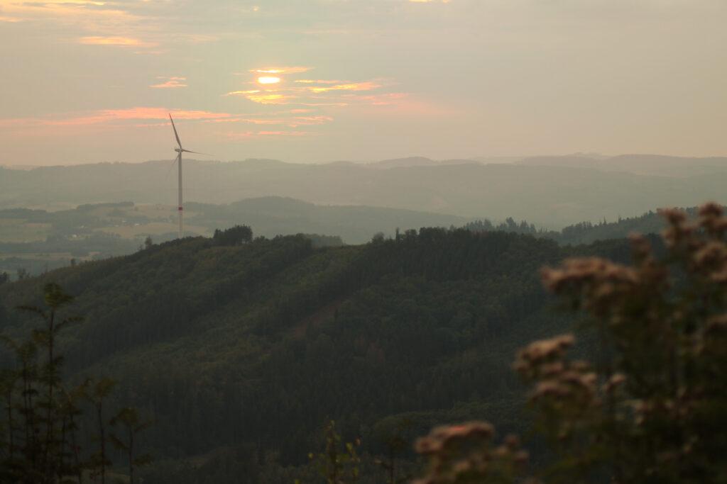 Sonnenuntergang von der Kuhhelle mit Blick auf das Windrad in Meggen