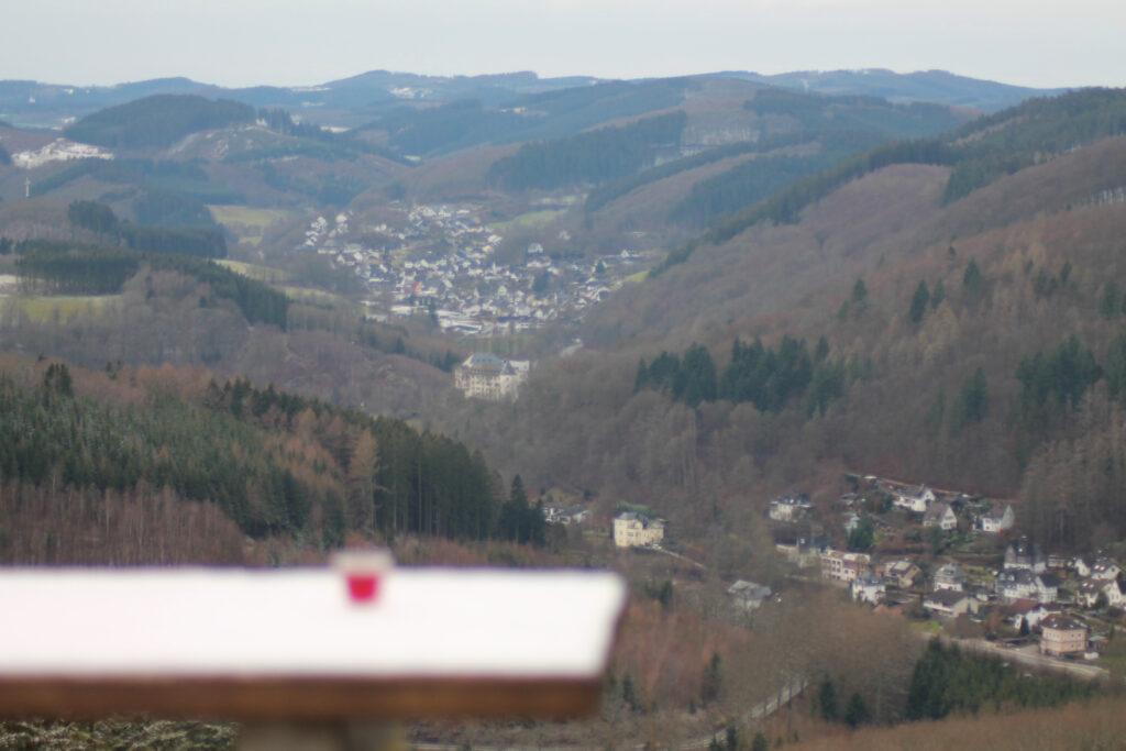 Pinnchen mit selbstgemachtem Schlehenlikör auf einem Tisch mit Blick auf Burg Bilstein