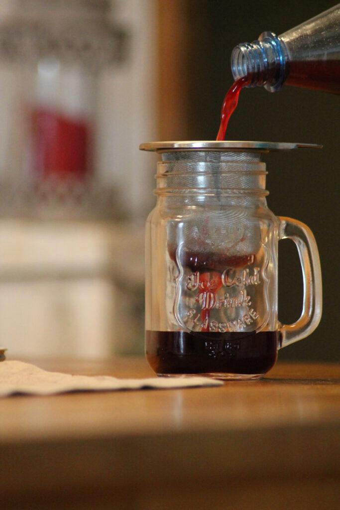 Aufgesetzter Schlehenlikör wird über ein feinmaschiges Teesieb filtriert.