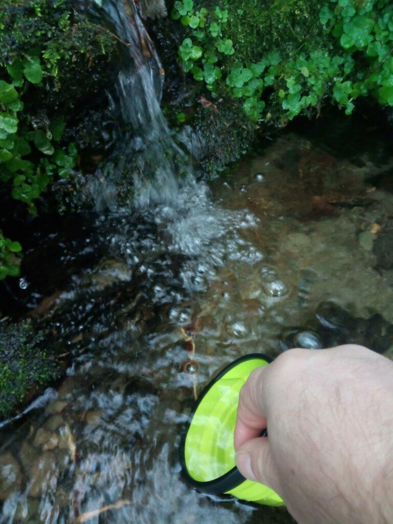 Wasser schöpfen an der Heiligenbornquelle im Winter mit dem Faltbecher