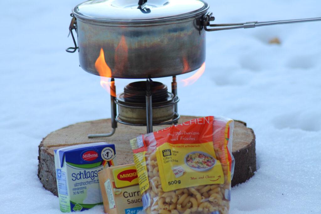 Zutaten für die One-Pot-Pasta vor dem Topf und Kocher im Schnee.