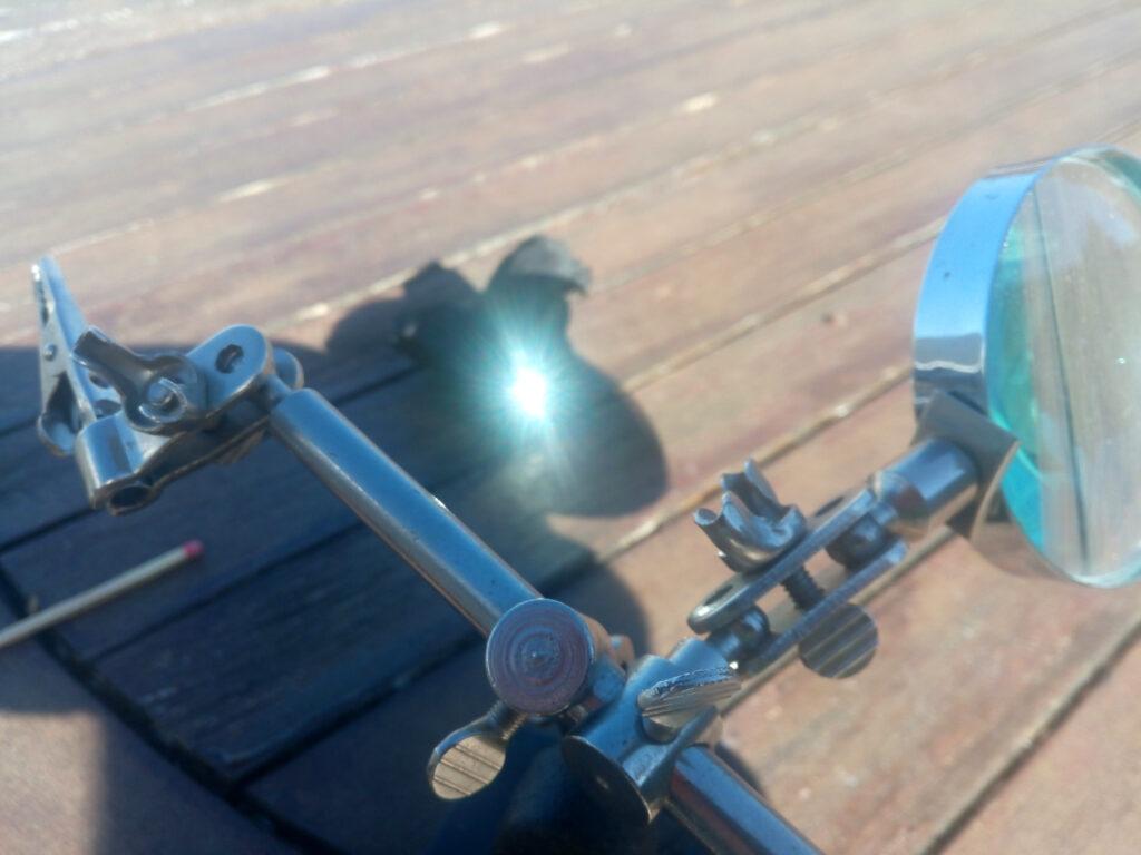 Größere Lupe auf der Terrasse. Gebündelte Sonnenstrahlen auf ein Stück Kohle und ein Streichholz.