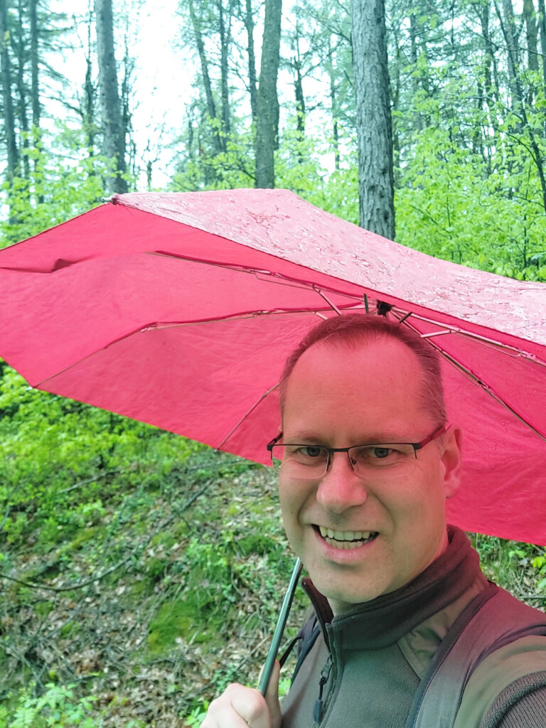 Wandern im leichten Regen mit Regenschirm.