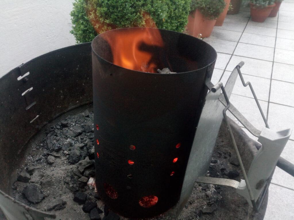 Mit einem selbstgebauten Dosenkocher werden die Grillkohlen im Grillkamin durchgeglüht.